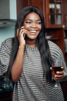 Portrait d'une belle jeune femme avec un verre de vin rouge en riant lors de la prise de téléphone avec son meilleur ami