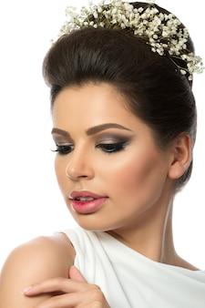 Portrait de belle jeune femme vêtue d'une robe blanche avec des fleurs de gypsophile dans ses cheveux isolated over white