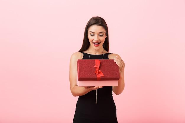 Portrait d'une belle jeune femme vêtue d'une robe noire debout isolé sur fond rose, boîte-cadeau ouverte