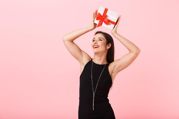 Portrait d'une belle jeune femme vêtue d'une robe noire debout isolé sur fond rose, tenant une boîte-cadeau sur sa tête