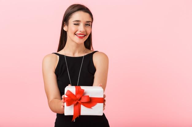 Portrait d'une belle jeune femme vêtue d'une robe noire debout isolé sur fond rose, tenant une boîte-cadeau