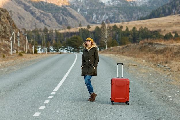 Portrait d'une belle jeune femme voyageur, debout au milieu de la route dans les montagnes à côté d'une valise rouge