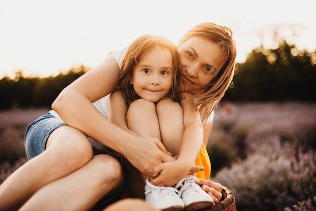 Portrait d'une belle jeune fille assise sur un banc dans un champ de lavande regardant la caméra en souriant tout en étant embrassée par sa mère contre le coucher du soleil.
