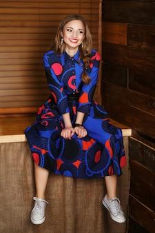 Portrait d'une belle jeune fille aux cheveux longs en robe bleue hétéroclite et gumshoes