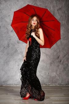 Portrait d'une belle jeune fille aux cheveux longs en robe de soirée noire avec un parapluie rouge
