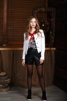 Portrait d'une belle jeune fille aux cheveux longs en short en cuir noir et une veste blanche