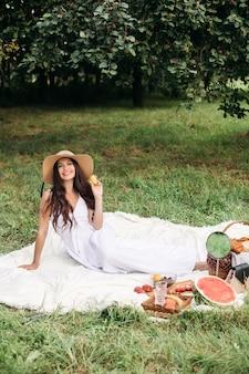 Portrait d'une belle jeune fille aux dents blanches même, un beau sourire dans un chapeau de paille et une longue robe blanche font un pique-nique dans le jardin