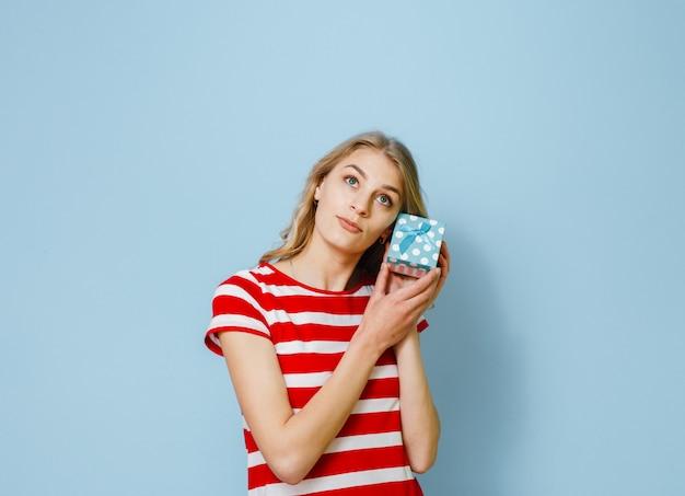 Portrait d'une belle jeune fille blonde excitée tenant un cadeau et heureux sur fond bleu