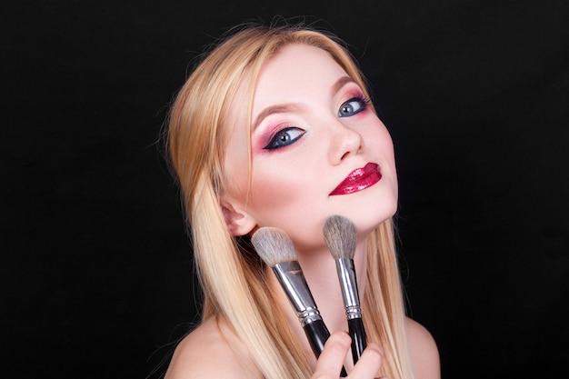 Portrait d'une belle jeune fille blonde avec des pinceaux pour le maquillage dans les mains sur fond noir