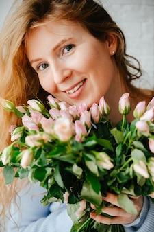 Portrait d'une belle jeune fille avec un bouquet de roses près de la fenêtre. cheveux roux bouclés.