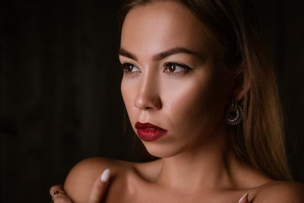 Portrait d'une belle jeune fille brune aux lèvres peintes et une boucle d'oreille sur fond noir