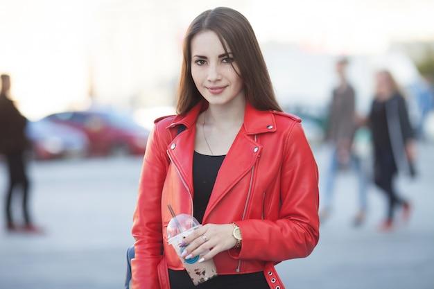 Portrait de la belle jeune fille brune marchant dans la rue. garder une boisson à emporter dans une main