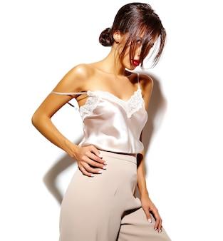 Portrait de la belle jeune fille brune sensuelle dans des vêtements classiques blancs élégants et un pantalon large sur fond blanc