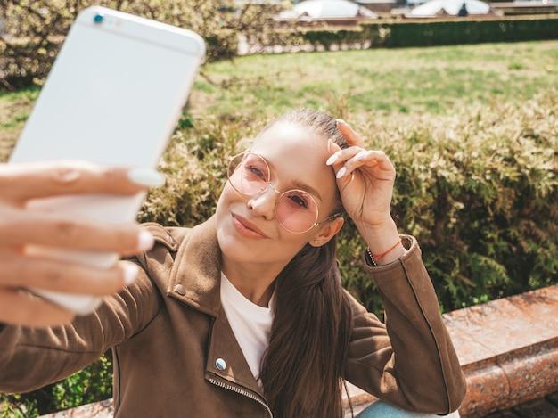 Portrait de la belle jeune fille brune souriante en veste et jeans hipster d'été modèle prenant selfie sur smartphone