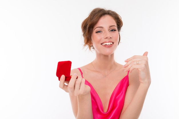 Portrait d'une belle jeune fille dans une robe rose essayant une bague sur un annulaire sur un fond blanc.