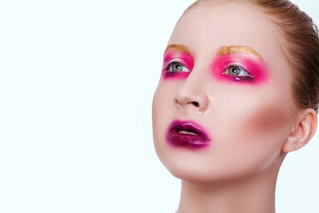 Portrait d'une belle jeune fille avec du maquillage créatif sur blanc