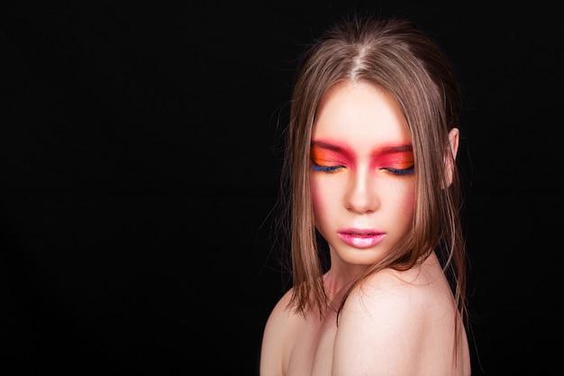 Portrait d'une belle jeune fille avec du maquillage rose sur fond noir