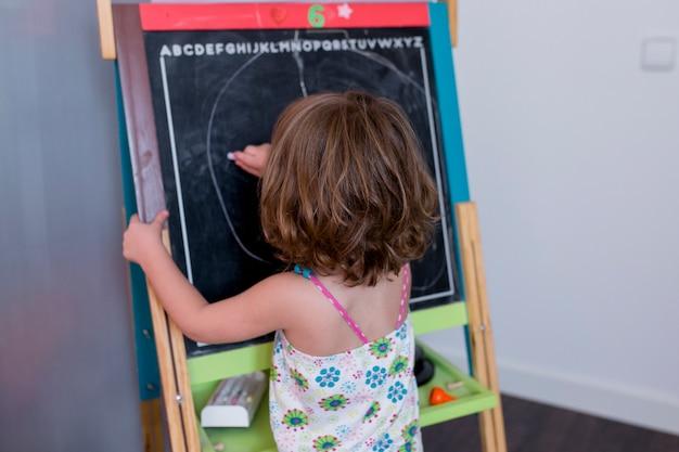Portrait d'une belle jeune fille enfant dessin sur le tableau noir à la maison. bonheur et style de vie à l'intérieur. été