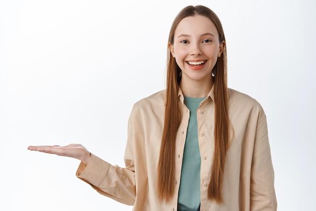 Portrait d'une belle jeune fille exposée à la main ouverte, tenant un article sur la paume et souriant, démontrant le produit, debout dans des vêtements décontractés contre un mur blanc