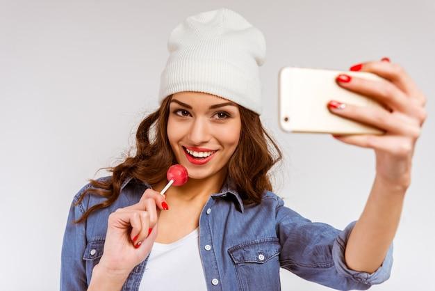 Portrait d'une belle jeune fille faisant selfie.