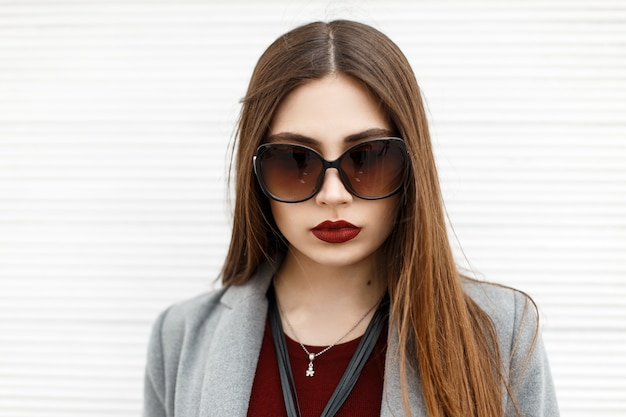 Portrait d'une belle jeune fille à lunettes de soleil dans la rue près d'un mur en bois blanc