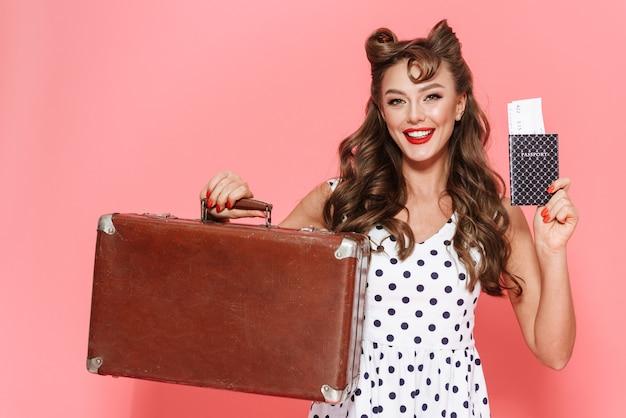 Portrait d'une belle jeune fille pin-up portant une robe debout isolé, montrant un passeport avec billet d'avion, transportant une valise