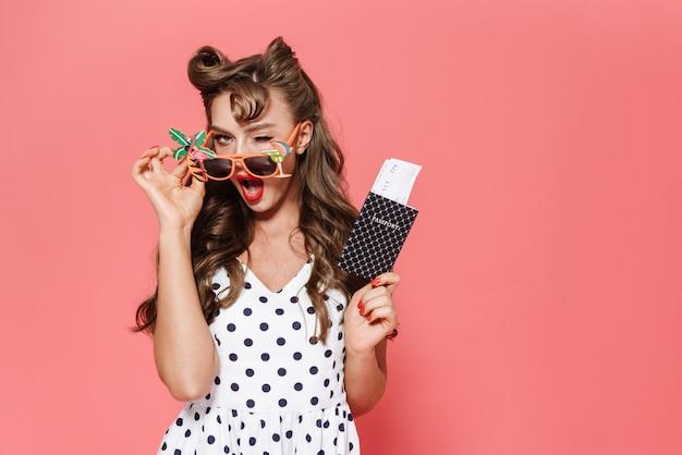 Portrait d'une belle jeune fille pin-up portant robe debout isolé, montrant le passeport avec billet d'avion