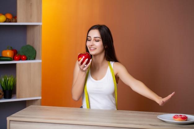 Portrait d'une belle jeune fille qui fait un choix entre une alimentation saine et nuisible