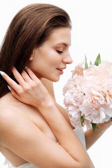 Portrait belle jeune fille souriante et posant avec des fleurs artificielles sur un mur blanc en robe blanche