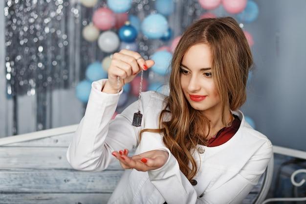Portrait d'une belle jeune fille en veste blanche assise sur un banc dans le studio avec des décorations de noël
