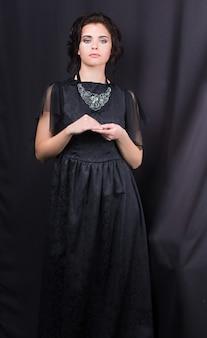 Portrait d'une belle jeune fille vêtue d'une robe noire, debout sur un fond sombre.