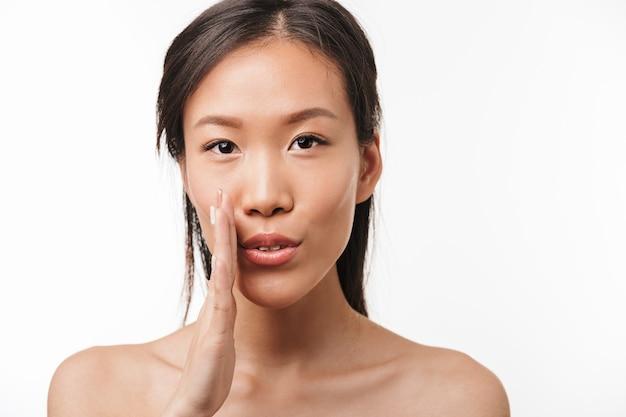 Portrait d'une belle jeune jolie femme asiatique choquée avec une peau saine posant isolée sur un mur blanc