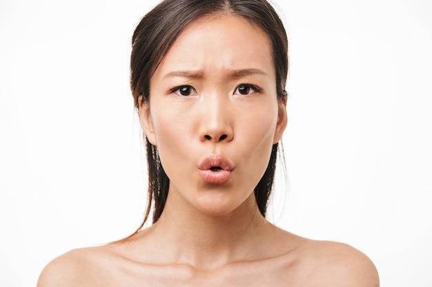 Portrait d'une belle jeune jolie femme asiatique excitée choquée avec une peau saine posant isolée sur un mur blanc