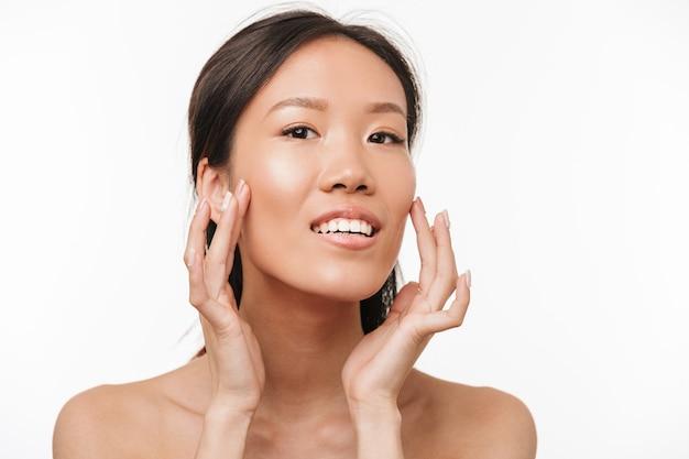 Portrait d'une belle jeune jolie femme asiatique positive joyeuse avec une peau saine posant isolée sur un mur blanc