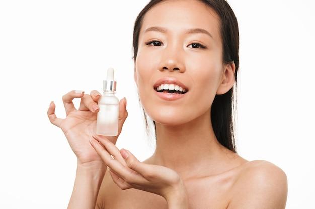 Portrait d'une belle jeune jolie femme asiatique positive avec une peau saine posant isolée sur un mur blanc tenant de l'huile de sérum