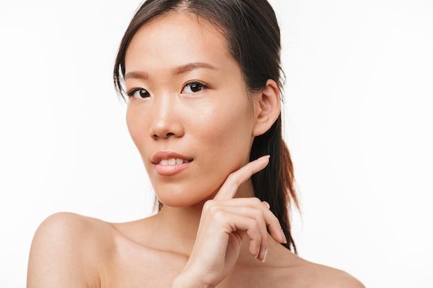 Portrait d'une belle jeune jolie femme asiatique positive avec une peau saine posant isolée sur un mur blanc