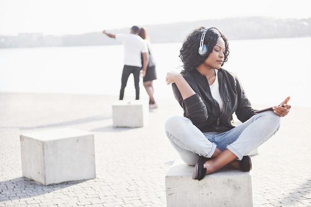 Portrait d'une belle jeune jolie fille afro-américaine assise sur la plage ou le lac et écouter de la musique dans ses écouteurs
