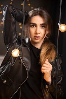 Portrait D'une Belle Jeune Mannequin En Blouson De Cuir Noir Posant Près Des Lampes. Photo gratuit