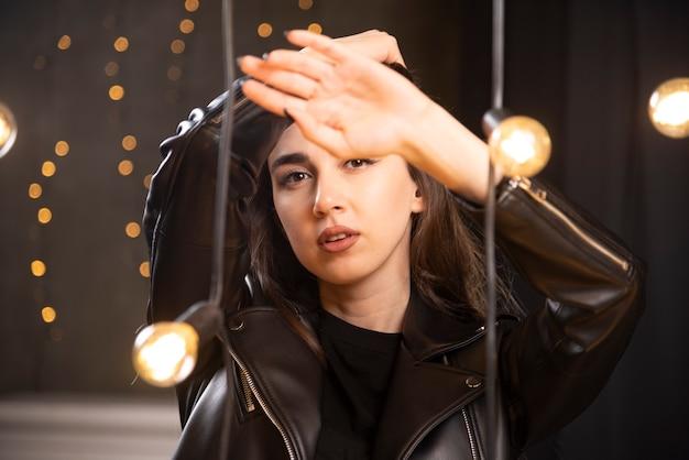 Portrait d'une belle jeune mannequin en blouson de cuir noir posant près des lampes.