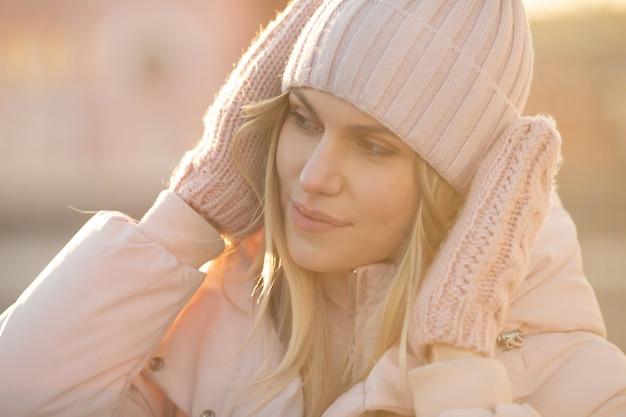 Portrait d'une belle jeune mannequin en bonnet rose et mitaines. belle jeune femme blonde souriante naturelle portant des gants tricotés
