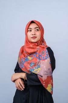 Portrait de la belle jeune mannequin dans un style hijab à la mode posant sur fond gris