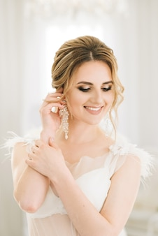Portrait d'une belle jeune mariée dans une pièce lumineuse dans une ambiance romantique. mariée en déshabillé avec des cheveux de mariage et du maquillage