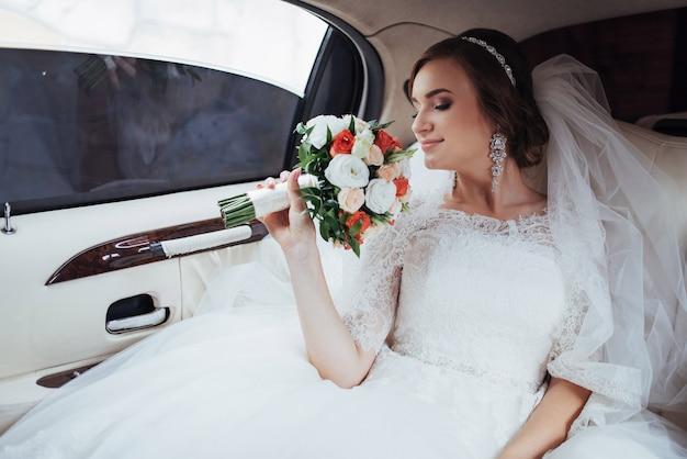 Portrait d'une belle jeune mariée dans la voiture