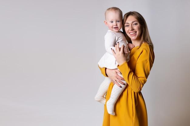 Portrait d'une belle jeune mère souriante avec un bébé dans ses bras