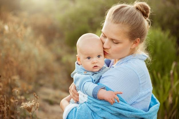 Portrait de la belle jeune mère tenant son bébé en bas âge