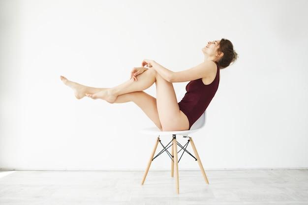 Portrait de la belle jeune modèle tendre en maillot de bain bordeaux souriant posant assis sur une chaise sur un mur blanc.