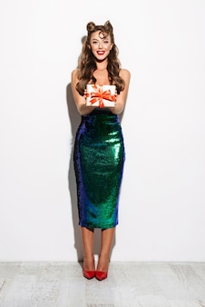 Portrait d'une belle jeune pin-up séduisante vêtue d'une robe debout isolé, montrant une boîte-cadeau