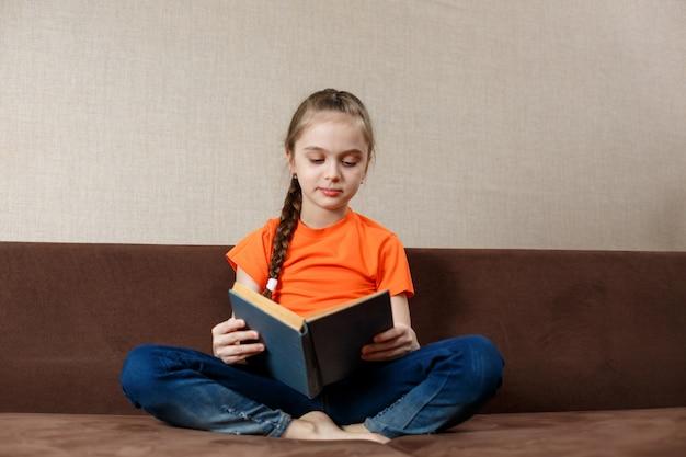 Portrait de belle jolie belle adolescente gaie concentrée portant un t-shirt orange assis en posture de lotus dans un canapé à la maison