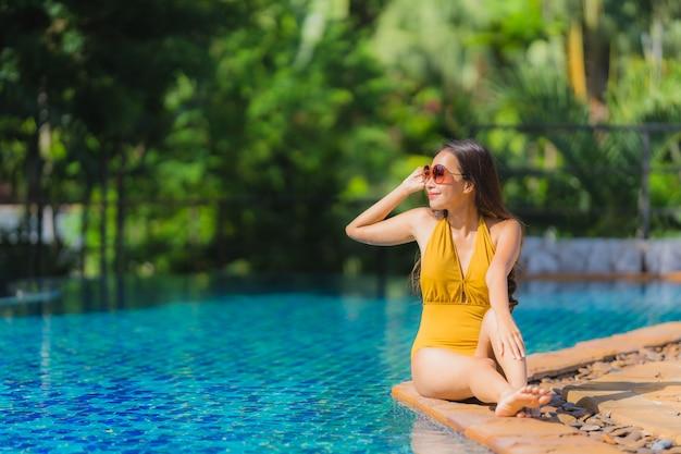 Portrait belle loisirs de jeune femme asiatique se détendre sourire et heureux autour de la piscine dans l'hôtel resort