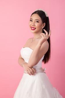 Portrait de la belle mariée asiatique en studio rose